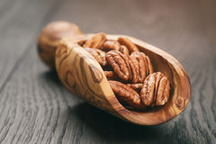 Pecan nuts in olive wood scoop on oak table Royalty Free Stock Images