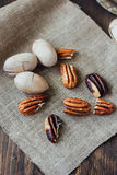Pecan nuts on piece of cloth over wooden table. Stock Images