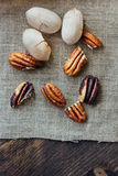 Pecan nuts on piece of cloth over wooden table. Royalty Free Stock Images