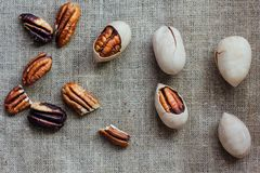 Pecan nuts on piece of cloth over wooden table. Stock Photos