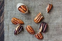 Pecan nuts on piece of cloth over wooden table. Royalty Free Stock Photography