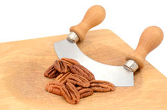 Pecan nuts with a rocking knife. Whole pecan nuts with a rocking knife on a wooden chopping board Stock Photos