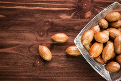 Pecan nuts in the shell in glass bowl on wooden background stock image