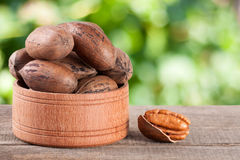 Pecan nuts in a wooden bowl on the old board with blurred garden background Royalty Free Stock Photos