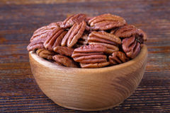Pecan nuts. In wooden bowl over wooden backgroundselective focus Stock Photos