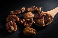 Pecan nuts with wooden spoon. Royalty Free Stock Images