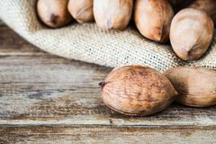 Pecan nuts on wooden table with pecans in gunny sack background. Close up shot Stock Images
