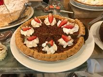Pecan Pie with Whipped Cream and Strawberries. A delicious pecan pie with whipped cream and fresh strawberries Royalty Free Stock Images