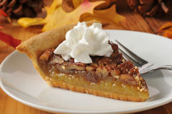 Pecan pie with whipped cream. Pecan pie topped with whipped cream on a colorful holiday table Royalty Free Stock Photos