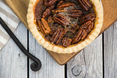 Pecan pie on wooden table, overhead view. Thanksgiving menu. Homemade small round caramel pecan pie served with vintage fork on the wooden background. Flat lay Stock Image
