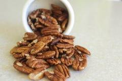 Pecannötter som spiller ut ur en behållare som placeras tätt lämnat Royaltyfri Foto