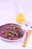 Pecans, chocolate pieces on a purple plate Royalty Free Stock Photography