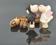 Pecans and kissing Sheep. Two kissing sheep and several pecans are on the gray specular background Stock Photos