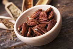 Pecans in the Wooden Bowl. Pecans in the Small Wooden Bowl with Other Spices in the Background Stock Images