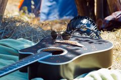 Pechera, Ukraine - 08.01.2015: acoustic guitar, black sunglasses, tambourine and djembe drum, hippie set at stage before concert stock photo