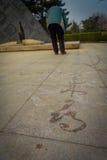 PECHINO, CINA - 29 GENNAIO 2017: La vecchia pittura cinese dell'uomo con acqua sulle mattonelle di pietra, nuovi anni tradizional Fotografie Stock