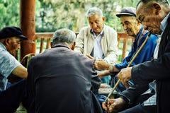 Pechino/Cina - 24 giugno 2011: carte da gioco cinesi anziane dell'uomo in un parco mentre una di loro che fumano un sigaro con un fotografia stock libera da diritti