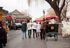 Pechino/Cina - 2019: La gente che cammina sulla via durante l'inverno Uomo che guida un risciò immagini stock