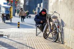 PECHINO, CINA - 10 MARZO 2016: Sulla sedia, sulla via, si Immagini Stock