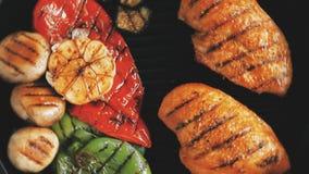 Pecho asado a la parrilla del prendedero del pollo con las verduras en la cacerola de la parrilla metrajes