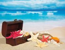 Pecho con las conchas de berberecho y las estrellas en arena de mar Foto de archivo libre de regalías
