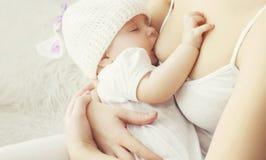 Pecho de alimentación de la madre suave de la foto su bebé fotos de archivo libres de regalías