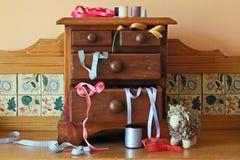 Pecho de cajones miniatura de madera con los utensilios de costura que lo rodean imagen de archivo
