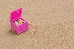 Pecho de juguete rosado con las cáscaras, en una playa arenosa, con el espacio de la copia, el verano y el concepto de la aventur foto de archivo libre de regalías