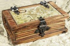 Pecho de madera con un mapa en su cubierta, en la arena Fotografía de archivo