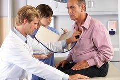 Pecho del doctor Listening To Male Patient's Foto de archivo libre de regalías