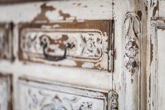 Pecho del vintage de cajones con la talla del color blanco con el descoloramiento y la manija del metal Primer Foco selectivo fotos de archivo libres de regalías