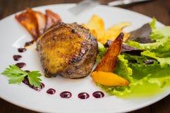 Pechuga de pato con las patatas fritas, las hierbas, la salsa y las manzanas caramelizadas Tabla rústica de madera Visión superio Imagen de archivo