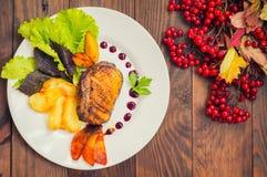 Pechuga de pato con las patatas fritas, las hierbas, la salsa y las manzanas caramelizadas Tabla rústica de madera Visión superio Fotos de archivo