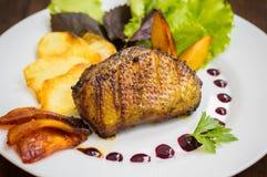 Pechuga de pato con las patatas fritas, las hierbas, la salsa y las manzanas caramelizadas Tabla rústica de madera Visión superio Fotografía de archivo