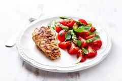 Pechuga de pollo asada a la parrilla con el espárrago y Cherry Tomato Salad con las hierbas y Chia Seeds Imagen de archivo