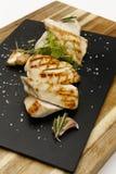 Pechuga de pollo asada suculenta sazonada, con la guarnición del ajo y del romero foto de archivo