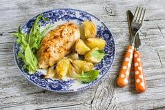 Pechuga de pollo cocida con las patatas y las cebollas en una placa del vintage Imagenes de archivo