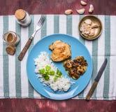 Pechuga de pollo con la salsa y el arroz de seta en una placa azul con una opinión superior del fondo rústico de madera del cuchi Imagen de archivo libre de regalías