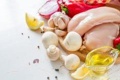 Pechuga de pollo e ingredientes en el fondo de madera blanco Foto de archivo libre de regalías