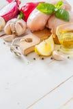 Pechuga de pollo e ingredientes en el fondo de madera blanco Imagen de archivo libre de regalías