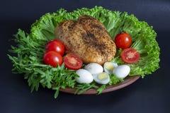 pechuga de pollo en las hojas de la lechuga con los tomates y los huevos de codornices foto de archivo