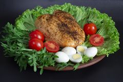 pechuga de pollo en las hojas de la lechuga con los tomates y los huevos de codornices imagen de archivo libre de regalías