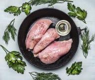 Pechuga de pollo fresca cruda sazonada con aceite e hierbas en un cierre rústico de madera del fondo de los sartenes viejos del a Fotografía de archivo