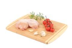 Pechuga de pollo y verduras crudas en el tablero de madera Fotografía de archivo