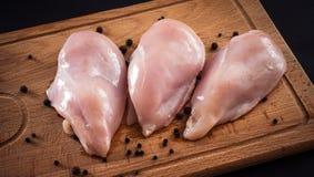 Pechugas de pollo y especias crudas en tabla de cortar de madera Foto de archivo libre de regalías