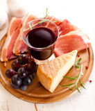 Pecorino Toscano and dry cured ham with red wine. On chopping board Royalty Free Stock Photo