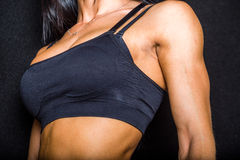 Pectorals. Body of a female bodybuilder showing her pectoral muscles. on black background Stock Photography