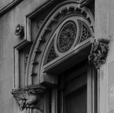 Peculiar animals standing beside the window on the capitals. Shot in black and white detail on the sculpture on the facade of this historic building representing Royalty Free Stock Images