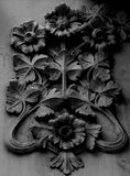 Peculiar branches shape with some flowers on it. Shot in black and white detail on the sculpture on the facade of this historic building representing some Royalty Free Stock Images