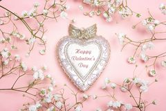 Peculiar heart with felicitation and small white flowers on pink. Background. Valentine`s day background Royalty Free Stock Photo